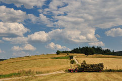 Harvest in mountain. Tractor on field and cloudy sky Stock Image