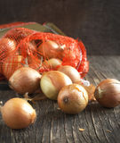 Harvest onions in sack on wooden background Royalty Free Stock Photos