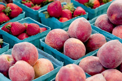 Harvest of peaches and strawberries at farmers market Royalty Free Stock Images