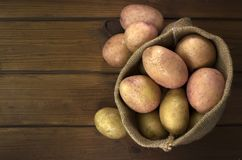 Harvest potatoes in burlap sack on wooden background Stock Photo
