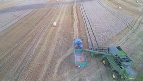 Harvest, pouring grain from the combine harvester, Poland, 08.2017, air. Pouring grain from the combine harvester, Poland, air, harvest of ripe cereal stock video footage
