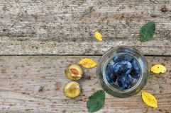 Harvest purple plums for canning in a glass jar on a wooden background, yellow and green leaves. rustic royalty free stock images