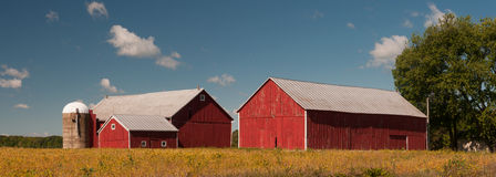 Harvest Season. Photograph of a couple of barns or outbuildings of a farm beneath the harvest skies of early autumn Stock Photography