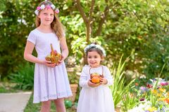 Jewish Holiday Shavuot.Harvest.Two little girls in white dress holds a basket with fresh fruit in a summer garden. stock photo
