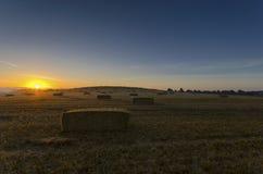 Harvest Sunrise. Sunrise over hay bales at harvest time Royalty Free Stock Images