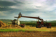 Harvest time. Hrvest time, tractor and combine on the golden field Stock Photos