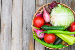 Harvest time. A basket of vegetables on a wooden table. Assorted colorful vegetables and herbs on the old wooden background , harvest time Royalty Free Stock Images