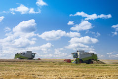 Harvest time. Harvesters working in a field Royalty Free Stock Photo