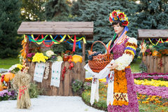 Harvest vegetables on fair trade in a wooden pavilion. Female mannequin holding basket full of fruits. Agricultural products, rura Stock Photo