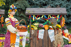 Harvest vegetables on fair trade in a wooden pavilion. Female mannequin holding basket full of fruits. Agricultural products, rura Stock Photos