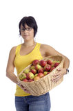 Harvest:young woman with basket full of apples Royalty Free Stock Photography