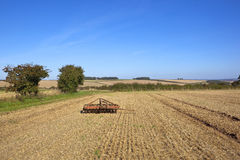 Harvested fields with farm machinery Royalty Free Stock Photos