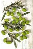 Harvested fresh olives with young olive twigs on wooden backgrou. Nd Royalty Free Stock Images