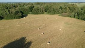 Harvested summer time farmland meadow with hay bales, aerial stock video footage