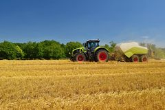Harvester agriculture machine harvesting golden ripe corn field. Tractor - hay and straw,  traditional summer background with an i Stock Photography