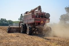 A harvester cutting dried, ripened soybeans on a family farm Stock Photo