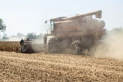 A harvester cutting dried, ripened soybeans stirs up a cloud of dust at harvest time. Royalty Free Stock Images