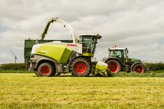 Harvester cutting field, loading Silage into a Tractor Trailer Stock Images