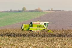 Harvester in the field in late fall. Shyroke, Ukraine - NOV 11, 2015: harvester in the field removes the corn stalks in late fall haze day Royalty Free Stock Image