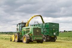 Harvester forager cutting field, loading Silage into a Tractor Trailer. John deere forager harvester cutting grass hay field, loading silage into a green tractor Royalty Free Stock Photos