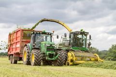 Harvester forager cutting field, loading Silage into a Tractor Trailer. John deere forager harvester cutting grass hay field, loading silage into a tractor Stock Photography