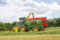 Harvester forager cutting field, loading Silage into a Tractor Trailer. John deere forager harvester cutting grass hay field, loading silage into a tractor Royalty Free Stock Images