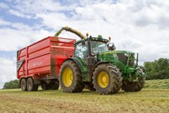 Harvester forager cutting field, loading Silage into a Tractor Trailer. John deere forager harvester cutting grass hay field, loading silage into a tractor Stock Photo