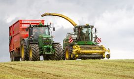 Harvester forager cutting field, loading Silage into Tractor Trailer. John deere forager harvester cutting grass hay field, loading silage into tractor trailer Stock Photo