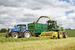 Harvester forager cutting field, loading Silage into a Tractor Trailer. John deere forager harvester cutting grass hay field, loading silage into a new holland Stock Photography