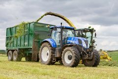 Harvester forager cutting field, loading Silage into a Tractor Trailer. John deere forager harvester cutting grass hay field, loading silage into a new holland Royalty Free Stock Photo