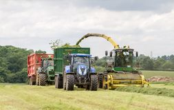 Harvester forager cutting field, loading Silage into a Tractor Trailer. John deere forager harvester cutting grass hay field, loading silage into two tractors Royalty Free Stock Photo
