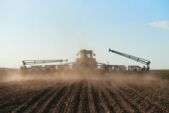 Harvester plowed soil sows seeds. Harvester goes far away. Selective focus Stock Image