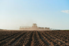 Harvester plowed soil sows seeds. Harvester goes far. Focus on ground Stock Photos