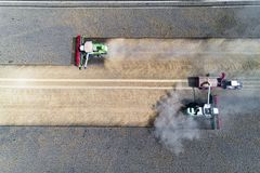 Harvester working on the field and filling the truck. Aerial view on the harvester working on the field and filling the truck Royalty Free Stock Images