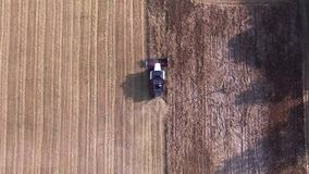 Harvester working in the fields. Top down view stock video