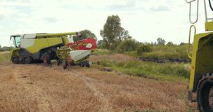 The harvesters have finished the harvest and go back to farming base. Prores, slow motion stock footage