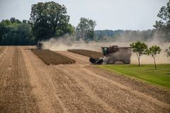 Harvesters at work on a family farm Stock Photo
