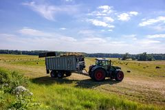 Kaluzhskiy region, Russia - June 2018: Harvesting of bales with agricultural equipment stock image