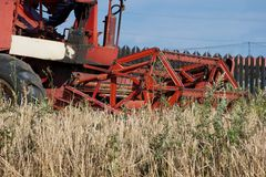 Harvesting combine resting on the field. Harvesting combine cutting  different grain in the field during the  fall Royalty Free Stock Photos