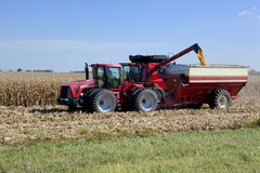 Harvesting Corn. Tractors harvesting a crop of corn for use in making ethanol additive for gas Royalty Free Stock Images