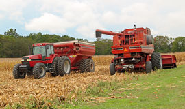 Harvesting Corn. Farm combine and a tractor and wagon harvesting corn Royalty Free Stock Image