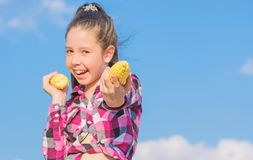 Harvesting and fun. Kids love corn food. Corn vegetarian and healthy organic product. Vegetarian nutrition concept. Kid. Girl hold yellow corn cob on sky royalty free stock photos