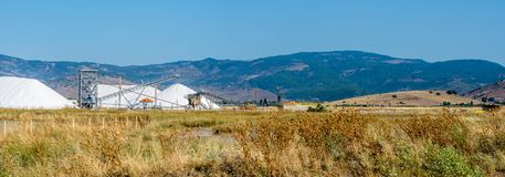 Harvesting salt on the flats between mountians and sea. Panoramic view of salt harvesting operation on the flats in a mountain valley royalty free stock photo