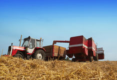 Harvesting time. With tractor and combine in a field Royalty Free Stock Photos