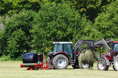 Harvesting and wrapping hay bales. A rotational plastic wrapping machine covering bales of freshly cut hay grass to be stored for winter fodder for livestock Royalty Free Stock Photo