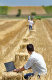 Harvesting. Young landowner with laptop supervising harvesting work Royalty Free Stock Photography