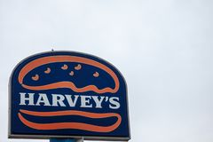Harvey`s logo, in front of one of their fast food in Montreal. stock photos
