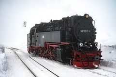 Harz/Germany-December 17 2017: Narrow gauge locomotive on the Brocken in a snowstorm royalty free stock images
