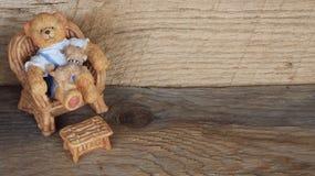 Harzteddybär, der in einem Stuhl auf einem hölzernen Hintergrund sitzt lizenzfreie stockfotos