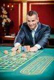 Hasardspelaren riskerar den leka rouletten på kasinot bordlägger Arkivbild